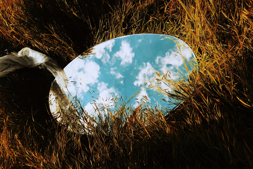 Mirror on grass reflecting clouds